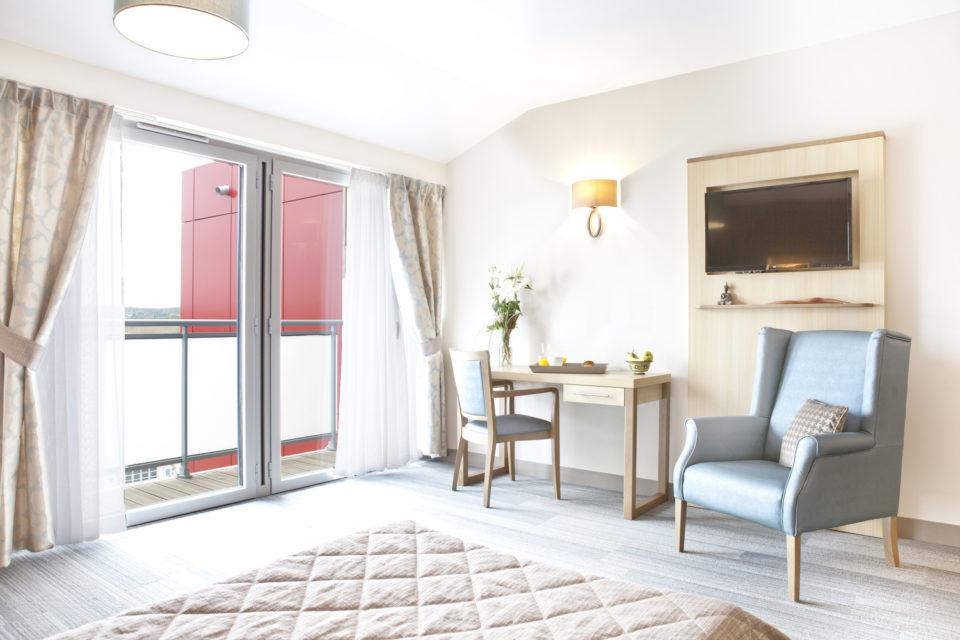 Photo prise depuis le lit où l'on voit une grande fenêtre avec une bonne luminosité - mobilier EHPAD