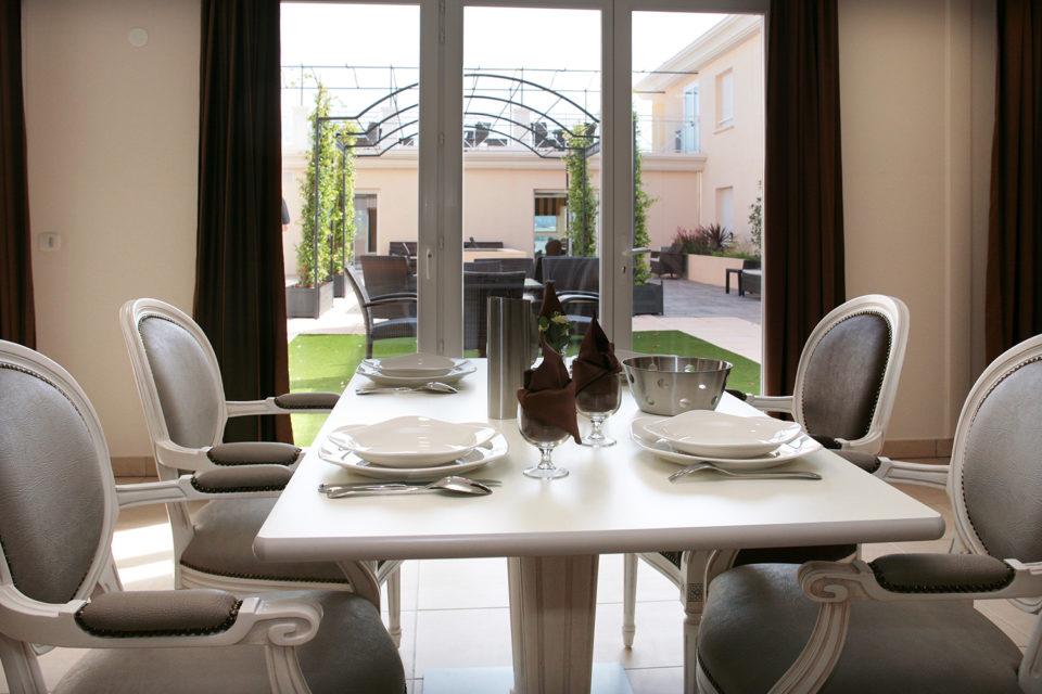 Mobilier pour chambre EHPAD où on peut voir une belle table avec des assises confortables autour