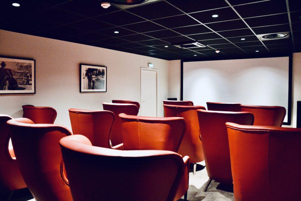 Salle de cinéma de l'EHPAD aménagée avec du mobilier maison de retraite et des assises rouges