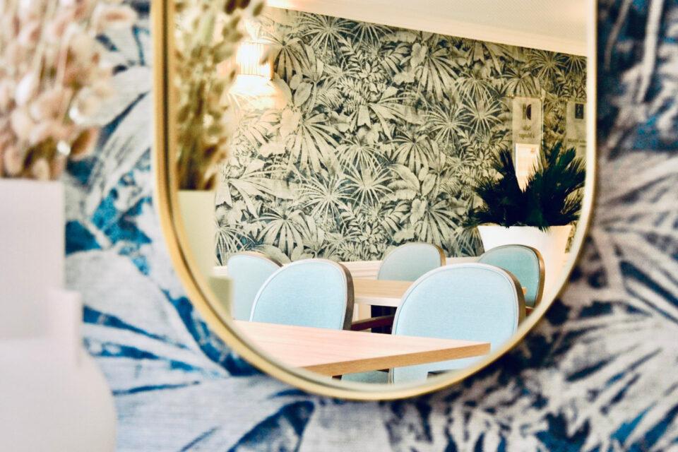Reflet dans un miroir où l'on voit des chaises bleues - Mobilier EHPAD