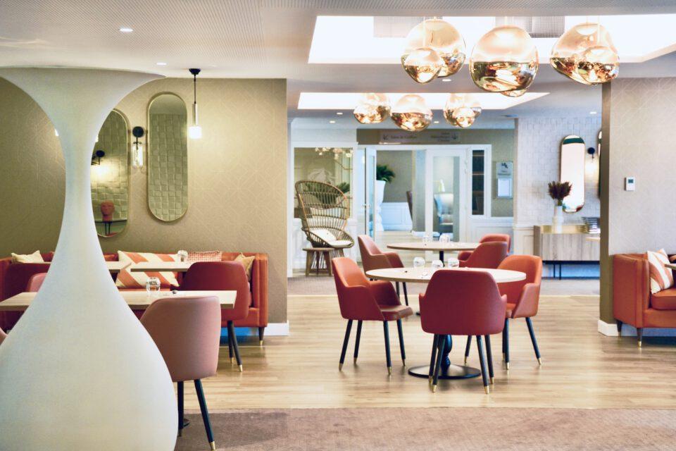 Une vue plus prés de la salle à manger où l'on voit des tables et de chaises dans les tons rouges
