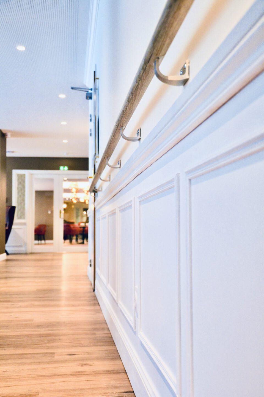 Le couloir bien aménagé grâce à la barre du mobilier maison de retraite - murs blancs et de belles lumières