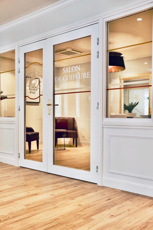Photo de l'entrée vitrée du salon de coiffure de l'EHPAD