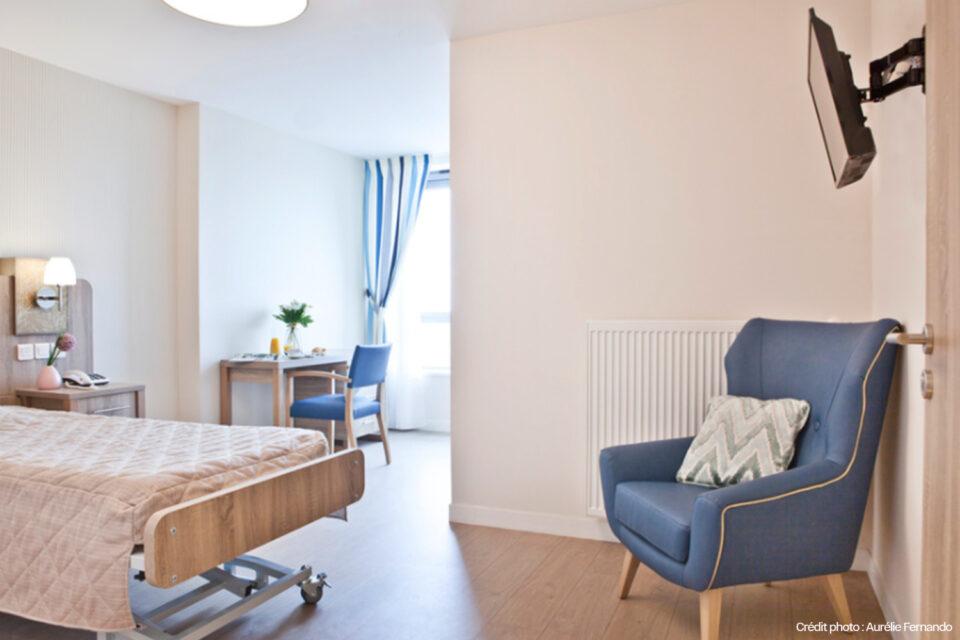 Une chambre EHPAD avec fenêtre laissant le soleil rentrer illuminer toute la pièce