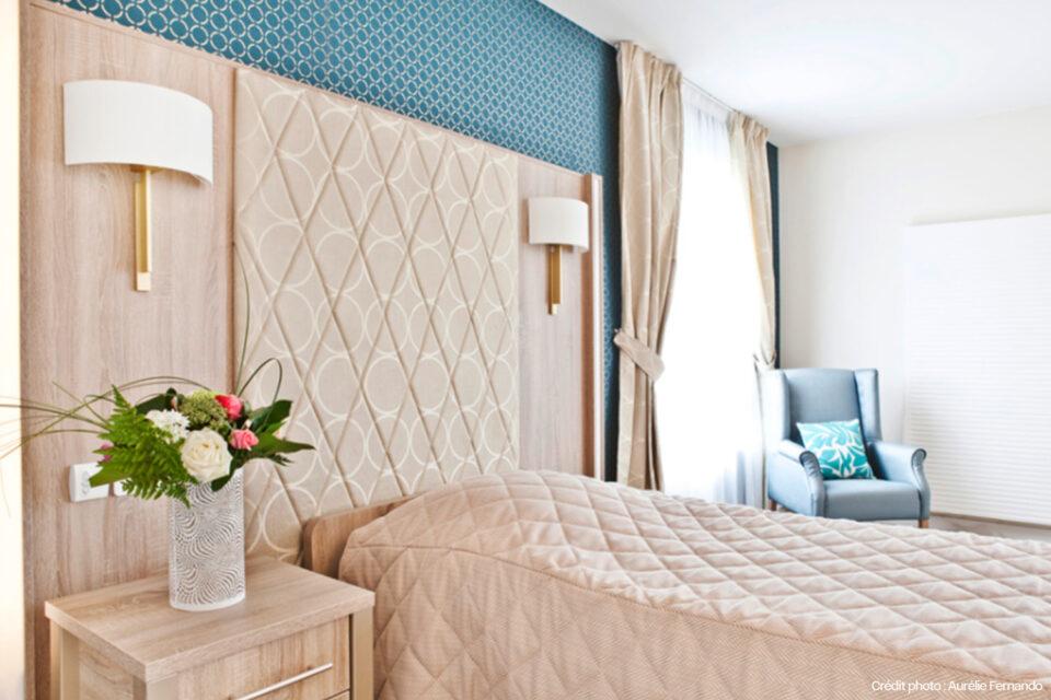 Une chambre d'EHPAD avec du mobilier EHPAD - lit et table de chevet