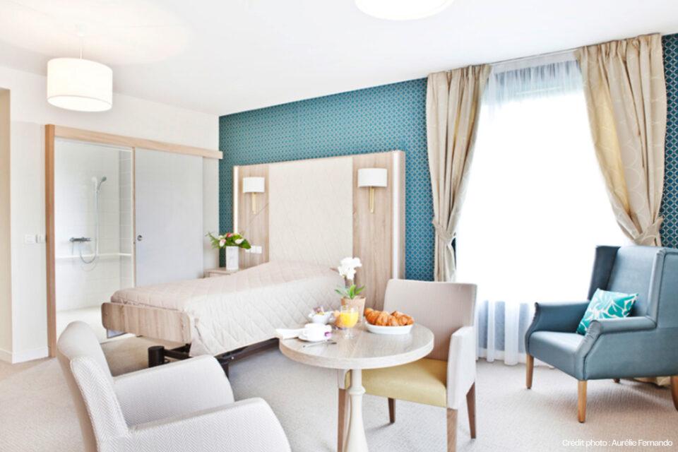 Une spacieuse chambre d'EHPAD avec lit, table et chaises