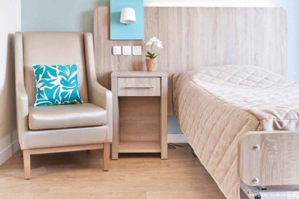 Un fauteuil à côté du lit d'une chambre d'EHPAD - du mobilier EHPAD de qualité