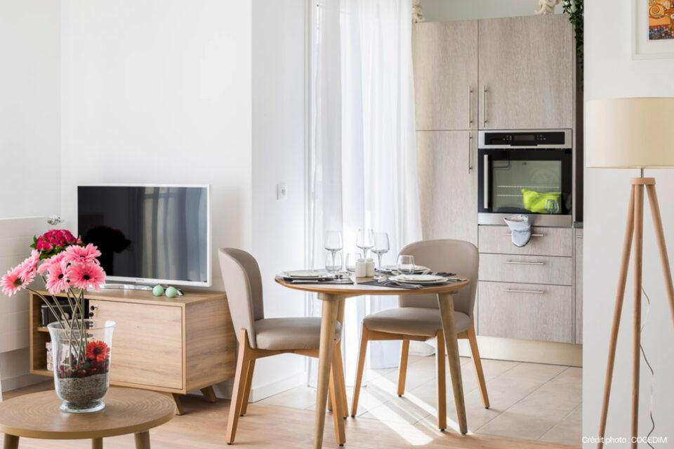 Superbe chambre décorée avec du mobilier pour EPHAD - On voit une table mise, une télé et la cuisine
