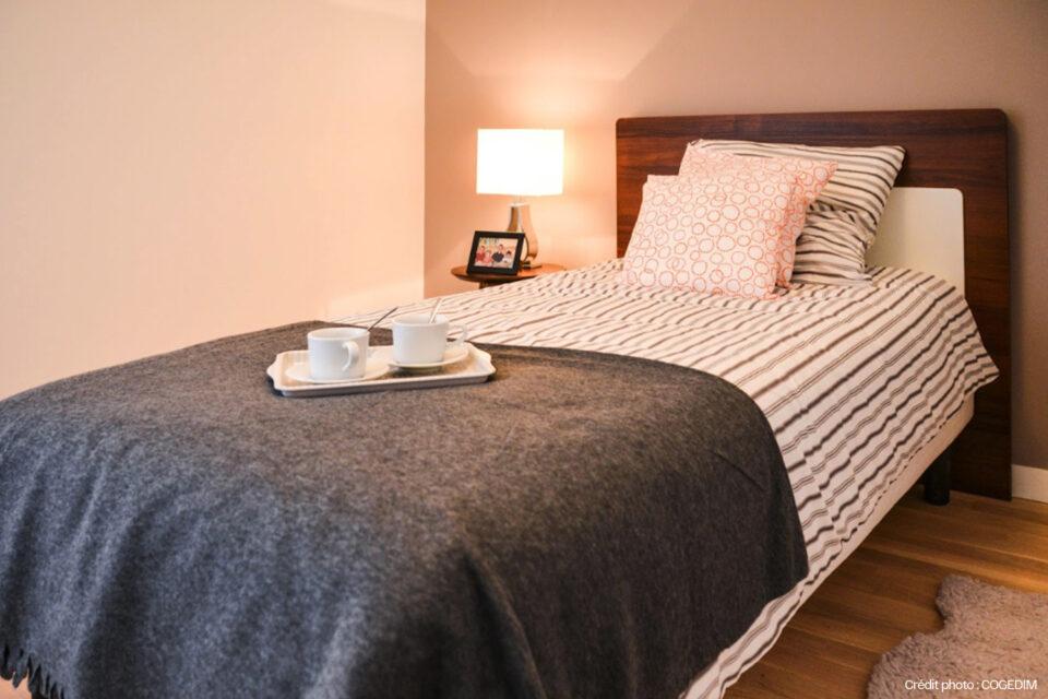 Chambre aménagée et confortable d'une résidence senior avec du mobilier et de la décoration EHPAD