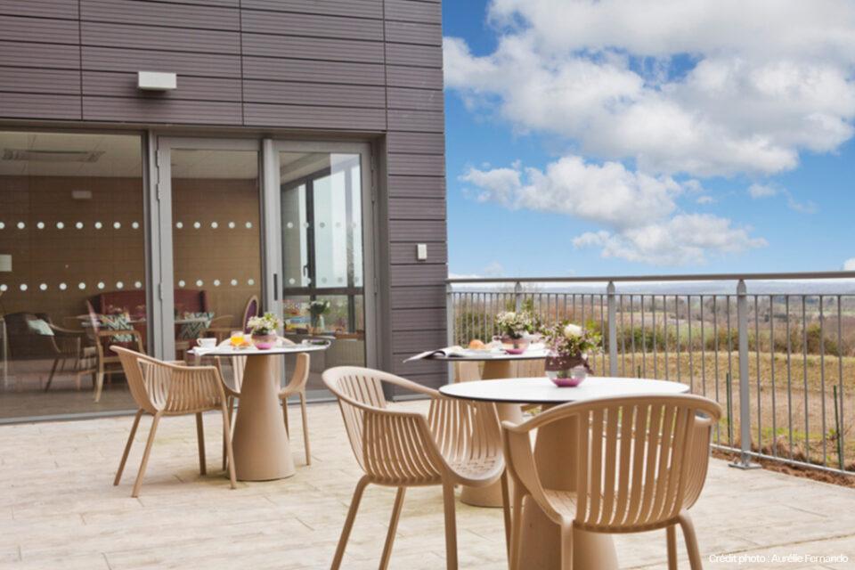 Terrasse d'un EHPAD avec du mobilier EHPAD de grande qualité et une vue dégagée magnifique