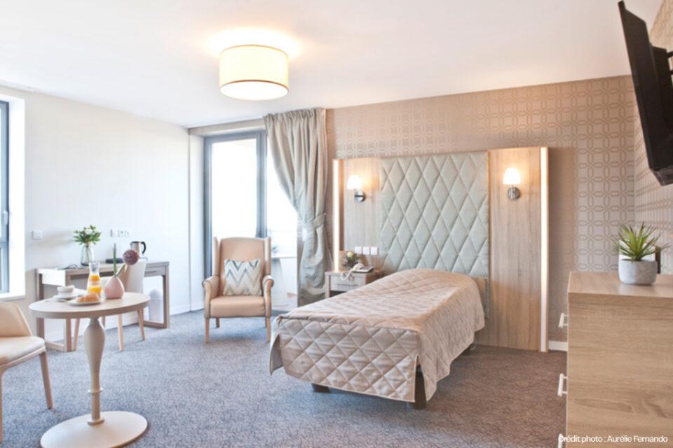 Chambre spacieuse avec du mobilier EHPAD tel que lit et fauteuils
