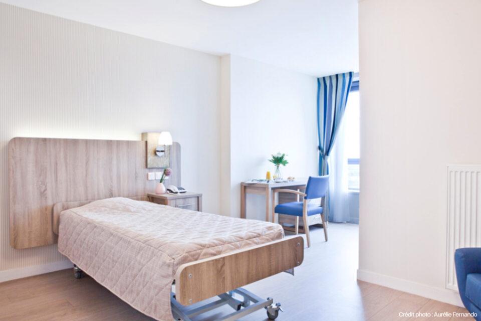 Photo d'une chambre EHPAD avec le lit fait